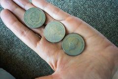 Tre monete tunisine sul woman& x27; palma di s Immagine Stock
