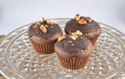 Tre muffin color cioccolato con i dadi sul vassoio di vetro Fotografia Stock Libera da Diritti