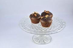 Tre muffin color cioccolato con i dadi sulla lastra di vetro Fotografia Stock Libera da Diritti