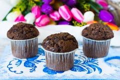 Tre muffin del cioccolato su un fondo dei fiori Fotografia Stock Libera da Diritti