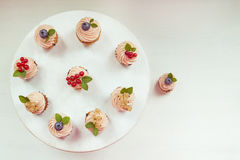 Tre muffin med kräm, kvisten av den vita vinbäret och mintkaramellen spricker ut; Arkivbild