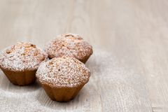 Tre muffin på den wood tabellen royaltyfria bilder