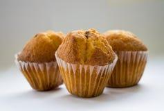 Tre muffin p? en vit bakgrund arkivbilder