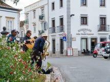 Tre musicisti della via che giocano musica di jazz ad una scena della via immagine stock