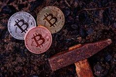 Tre mynt av bitcoin på svart jord och en hammare royaltyfri foto