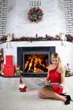 Tre nätt sexiga flickor som slitage Santa Claus, katt- och kaninkläder Ung härlig blond kvinna som läser en bok nära en spis Spis royaltyfri foto