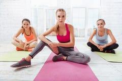 Tre nätta flickor som poserar i en konditionstudio Royaltyfri Bild