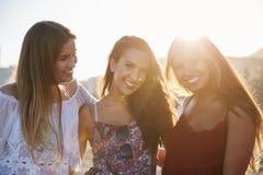 Tre nätta kvinnliga vänner som tillsammans står på att le för strand arkivbild
