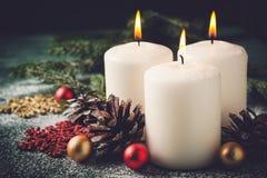 Tre Natali che bruciano le candele ed il primo piano delle decorazioni Immagini Stock