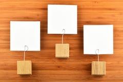 Tre note di carta con i supporti hanno isolato il fondo di legno di bambù Immagine Stock