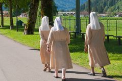 Tre nunnor som g?r p? en asfaltv?g fotografering för bildbyråer