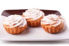 Tre nya muffin på den isolerade plattan Arkivfoto