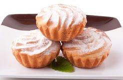 Tre nya muffin på den isolerade plattan Royaltyfria Bilder