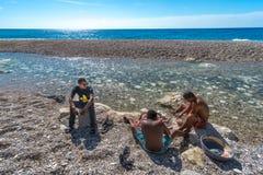 Tre oidentifierade pojkar som gör ren den nytt fångade fisken på Playa Sana Rafael i Dominikanska republiken Royaltyfri Foto