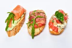 Tre olika bruschettes med gräsplaner, ost, kött och fisken Arkivbild
