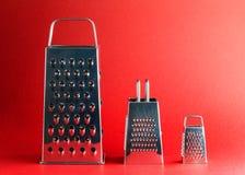 Tre olika formatrivjärn i beställning på röd bakgrund royaltyfri foto