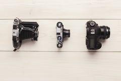 Tre olika kameror på den vita tabellen Royaltyfria Foton