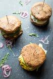 Tre olika smakliga stora hamburgare på mörk stenbakgrund Royaltyfri Bild