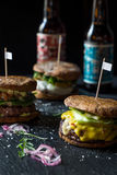 Tre olika smakliga stora hamburgare på mörk stenbakgrund Arkivfoto