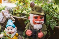Tre olika trädgårds- gnomer som föreställer olika ögonblick Arkivfoto