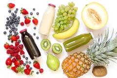 Tre olika typer av nya fruktsafter eller smoothies i flaskor och ingredienser som isoleras på vit bakgrund Royaltyfria Bilder