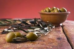 Tre olive sistemate con la ciotola e le foglie ceramiche Fotografie Stock