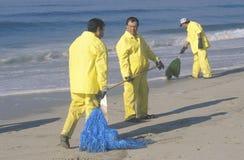 Tre oljerengöringsarbetare som upp gör ren stranden Arkivfoto