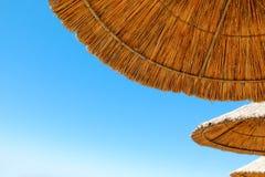 Tre ombrelli di spiaggia fatti di paglia al fondo del cielo blu Immagine Stock