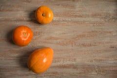Tre orange pumkins på träbrädena arkivfoton