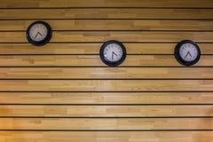 Tre orologi neri rotondi sulla parete dei bordi gialli grigio chiaro di legno Linee orizzontali struttura di superficie naturale immagini stock libere da diritti