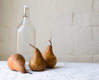 Tre päron med glasflaskan Royaltyfri Foto