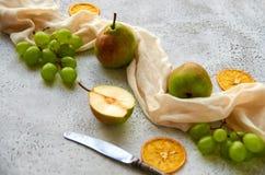 Tre päron med gröna druvor och tre torkade stycken av apelsinen som dekoreras med silvertappningkniven och ljus - brun torkduk Royaltyfri Fotografi