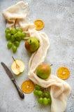 Tre päron med gröna druvor och tre torkade stycken av apelsinen som dekoreras med silvertappningkniven och ljus - brun torkduk Royaltyfri Bild