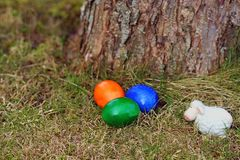 Tre påskägg och ett vitt keramiskt får bredvid en trädstam royaltyfri fotografi