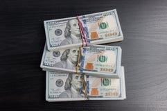 Tre pacchetti dei dollari di diecimila su una tavola di legno scura Vista da sopra immagine stock libera da diritti
