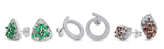 Tre paia degli orecchini d'argento del perno delle forme differenti su un fondo bianco Fotografia Stock