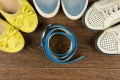 Tre paia delle scarpe e della cinghia del ` s delle donne sul pavimento marrone sono a Fotografia Stock