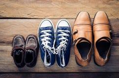 Tre paia delle scarpe, tre fasi della crescita Fotografia Stock