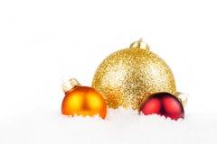 Tre palle di natale che mettono su neve Fotografia Stock