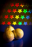 Tre palle gialle di Natale sul fondo delle stelle di colore luminoso Immagine Stock