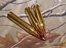 Tre pallottole del fucile con un fondo di camo Fotografie Stock Libere da Diritti