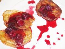Tre pancake con lo sciroppo della ciliegia sulla zolla Immagini Stock