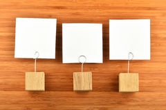 Tre pappers- anmärkningar med hållare på träbakgrund Royaltyfria Foton