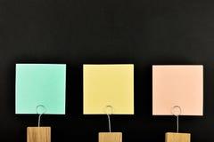 Tre pappers- anmärkningar med hållaren som isoleras på svart för presentation Arkivbilder