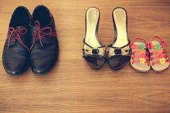 Tre par av skor: män, kvinnor och barn Behandla som ett barn sandalställningen bredvid kvinnors skor Arkivfoto