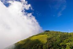 Tre parti di nuvola, il cielo blu e il moutain alzano alla montagna di Inthanon, Tailandia Fotografie Stock