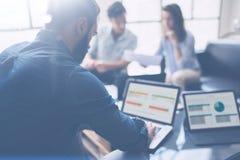 Tre partner che fanno ricerca per la nuova direzione di affari Giovane uomo d'affari che lavora computer portatile moderno e che  immagini stock libere da diritti