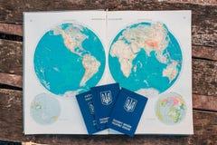 Tre passaporti sui precedenti della mappa di mondo Il viaggio comincia fotografie stock