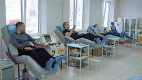 Tre pazienti donano il sangue in una clinica moderna, facendo uso di attrezzatura medica stock footage