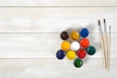 Tre pennelli e contenitori variopinti di gouache su superficie di legno nella vista superiore Fotografia Stock